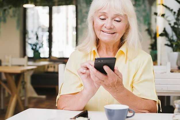 aged-woman-using-smartphone-home_23-2148216458